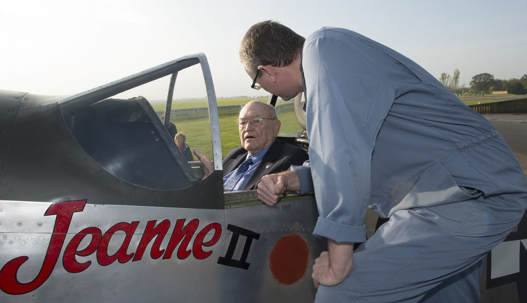 a photo of an elderyl man seated in the cockpit of a Mustang fighter talking to a man in a boiler suit