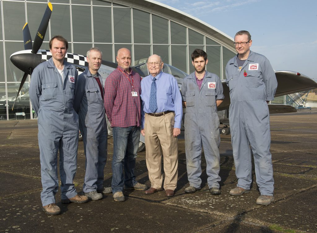 a photo of an elderly man flanked by men in boiler suits