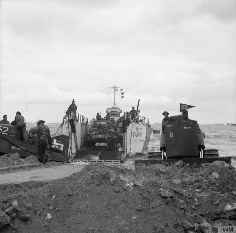 a black and white photo of tanks coming ashore from a alrge open-fronted craft