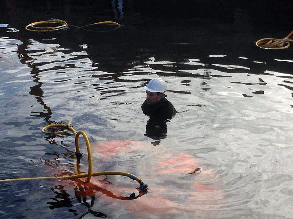 a photo of a diver in a hard had submerged in water