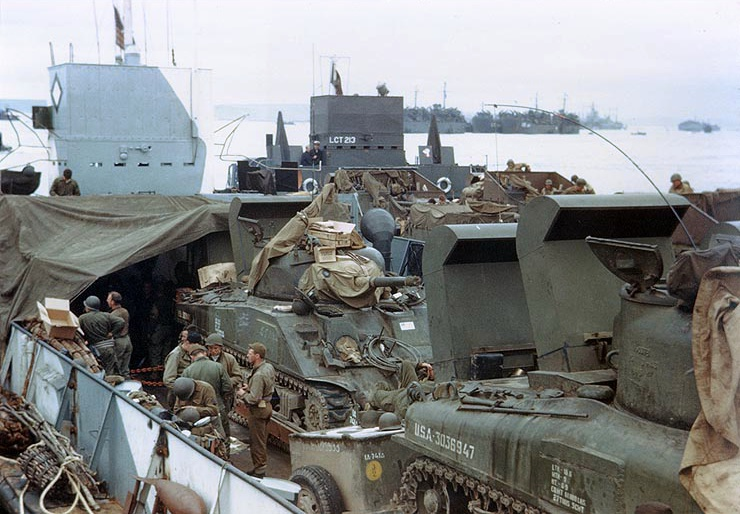 a colour photograph of tanks and troops on abord a large landing craft
