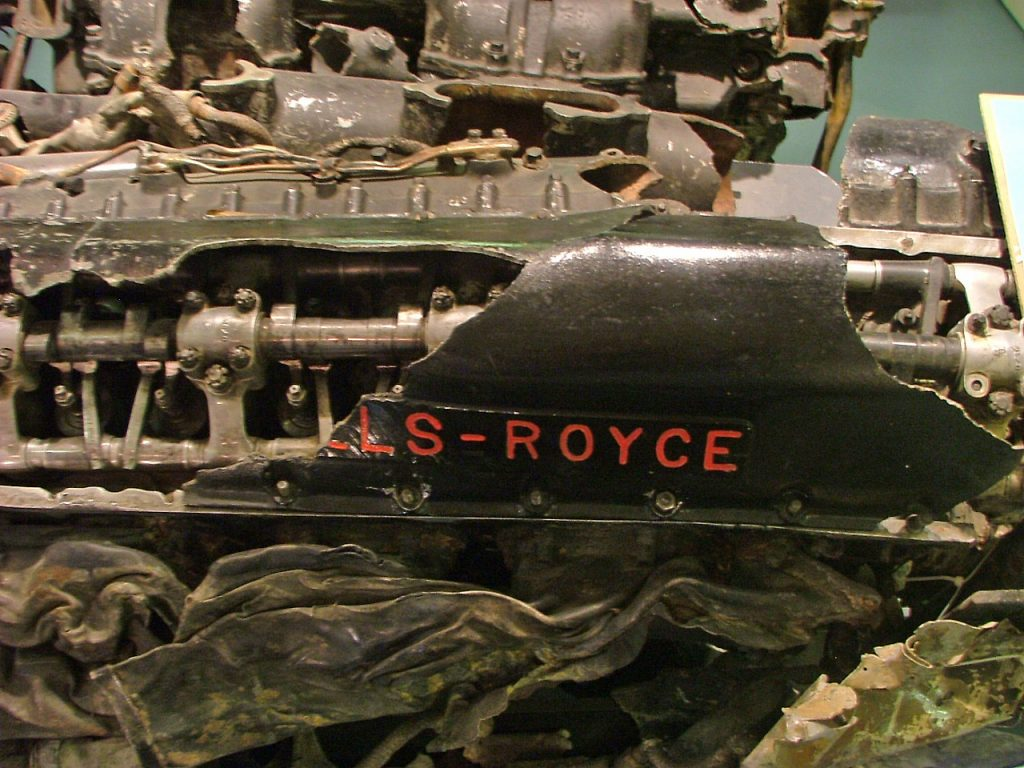 a photo of an engine cover with the words Rolls Royce in red imprinted upon it