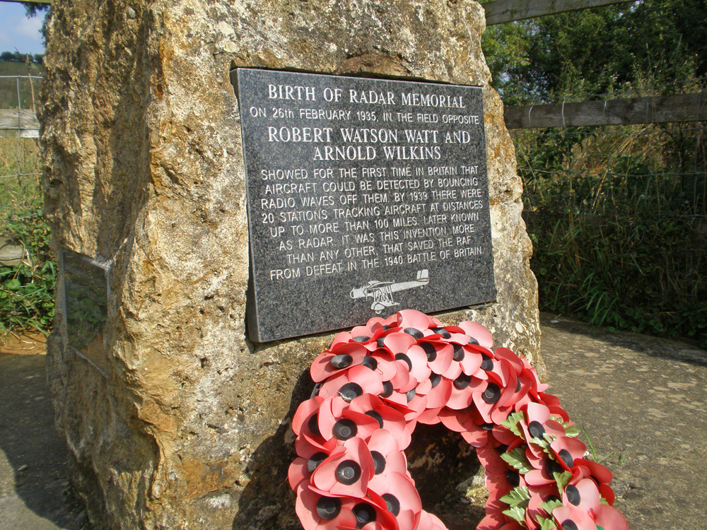 A photo of a memorial, a slate plaque embedded on a rock with a wreath of poppies at the foot.