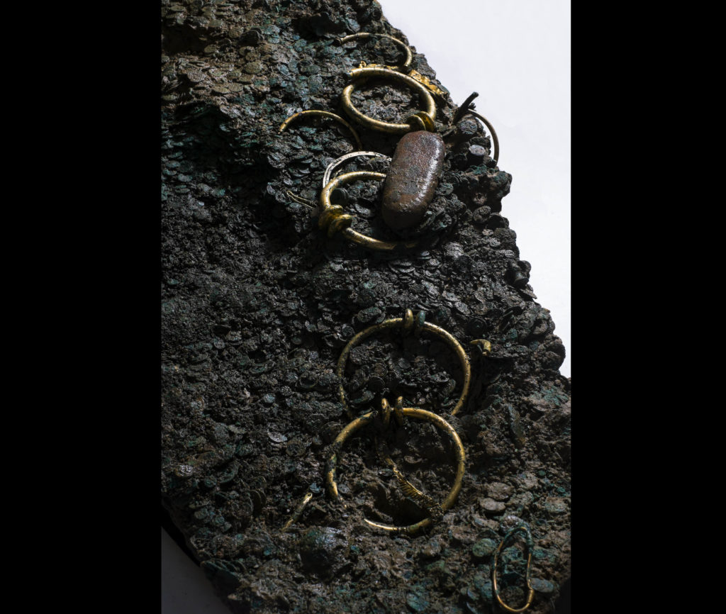 a photo of a hoard of rings with golden pieces of torc within it