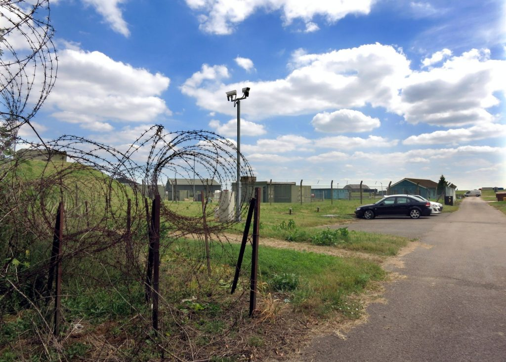 a phot of an airfield with barbed wire and piquets in the foreground