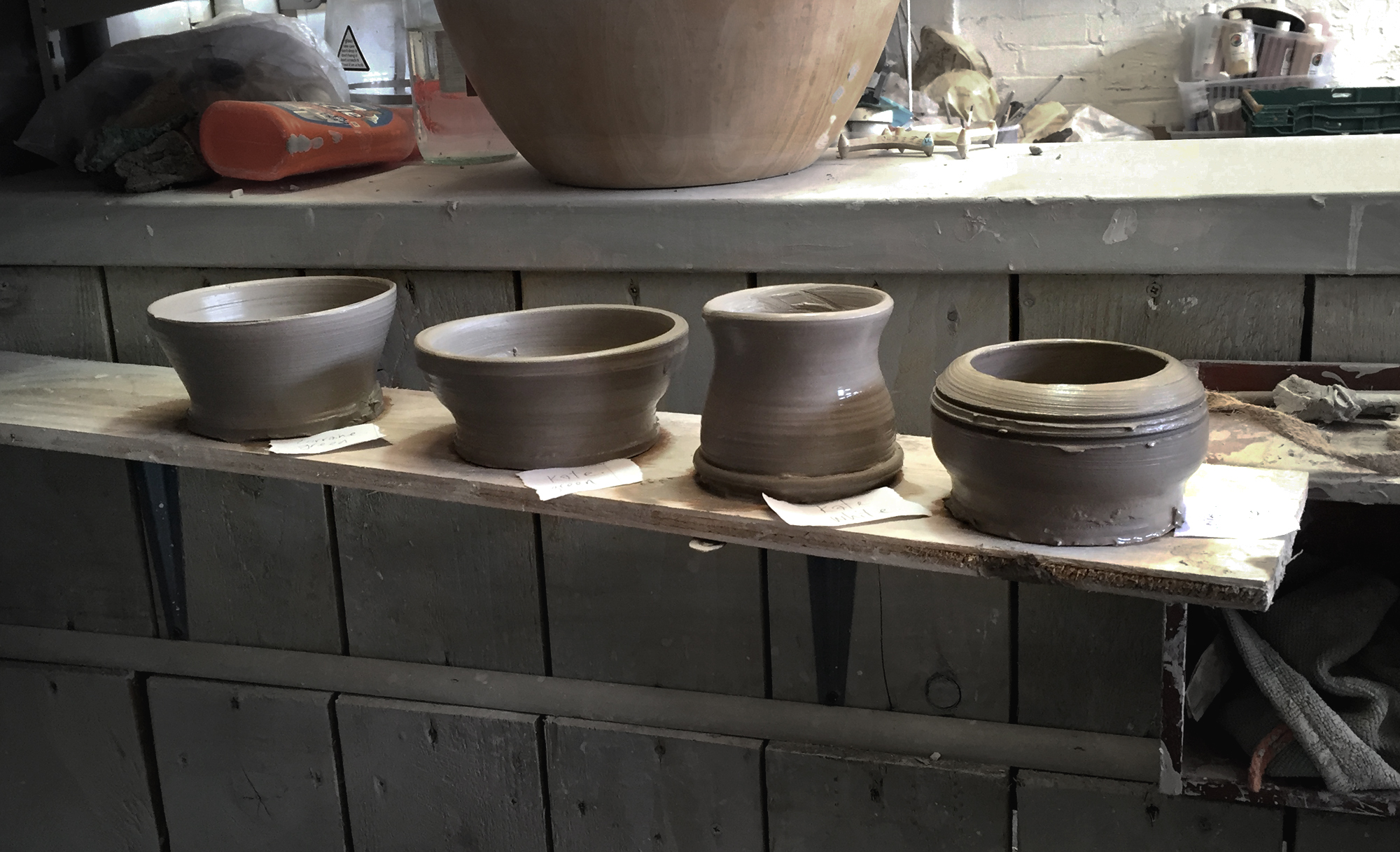Photograph of four thrown pots on a shelf
