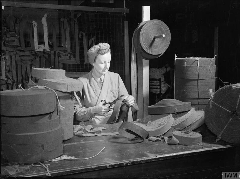 a photo of a woman in a headscarf cutting strips of material at a desk