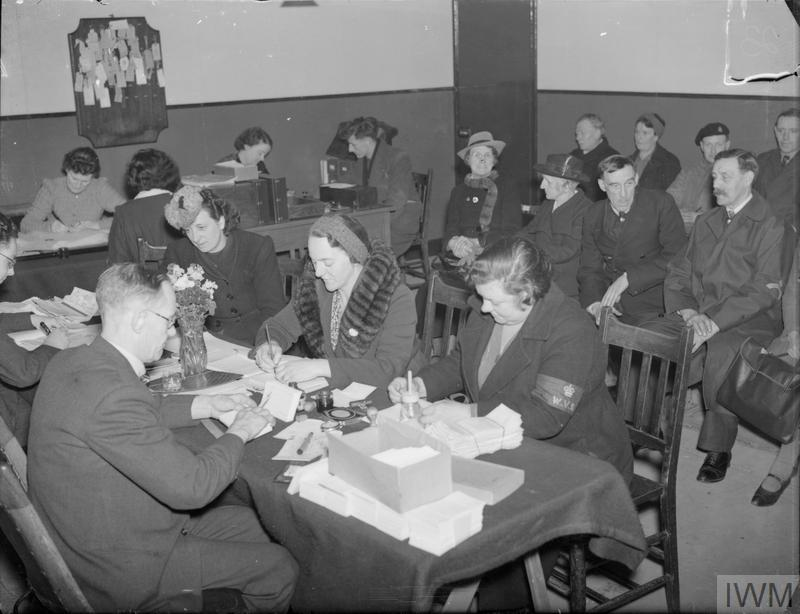 a photo of a room full of people with three women filling forms in at a desk