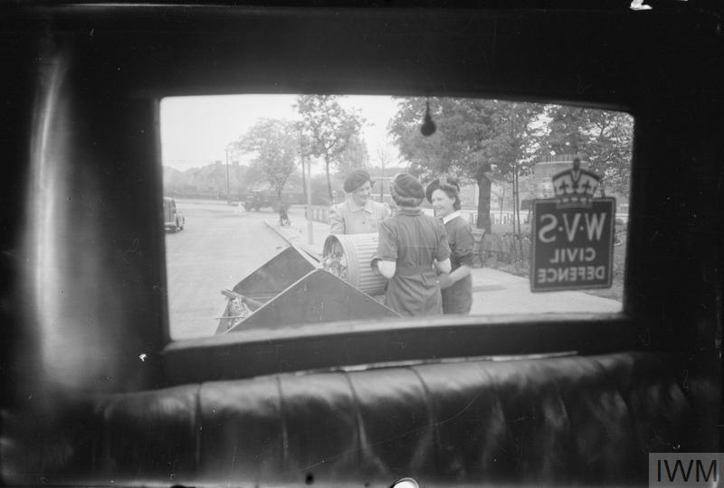a view of women talking to each other seen throough the rear window of a car