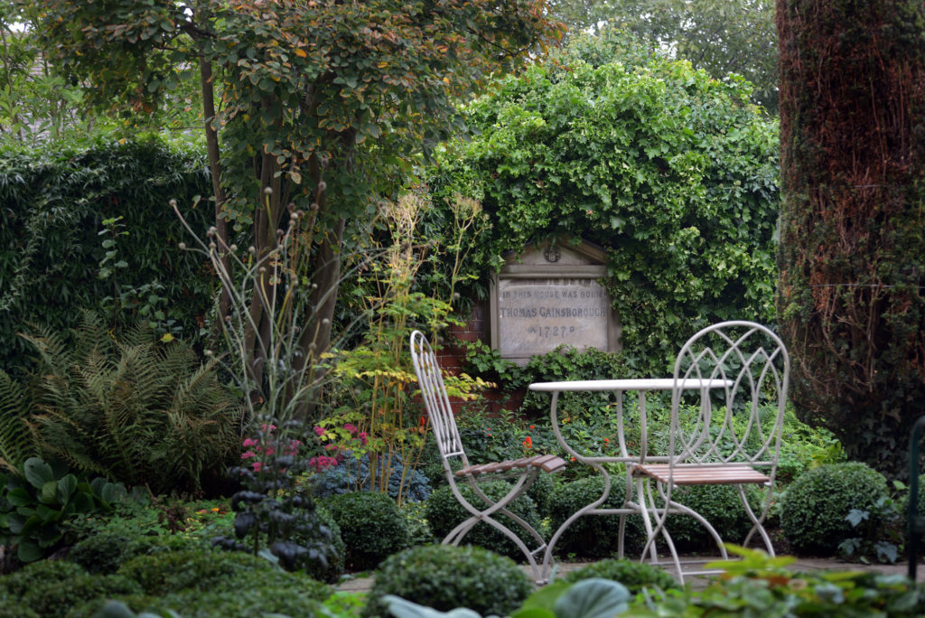 photograph of garden with table and chairs and plaque to thomas gainsborough