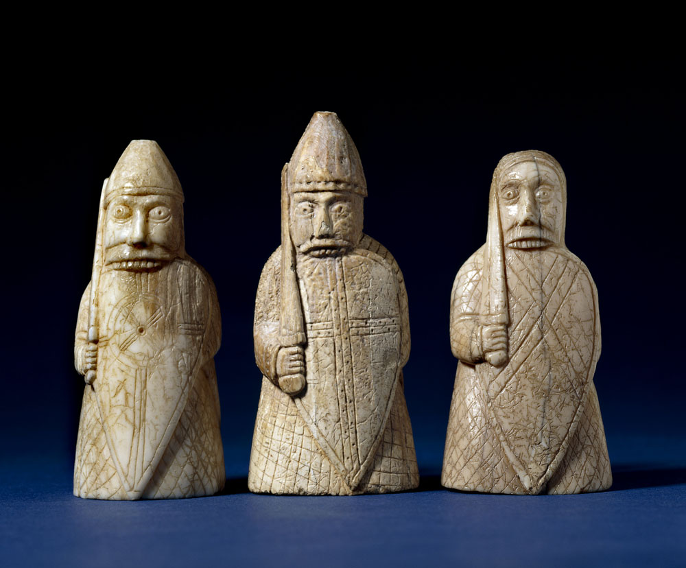 Three chess pieces carved into the shape of men, biting their shields.