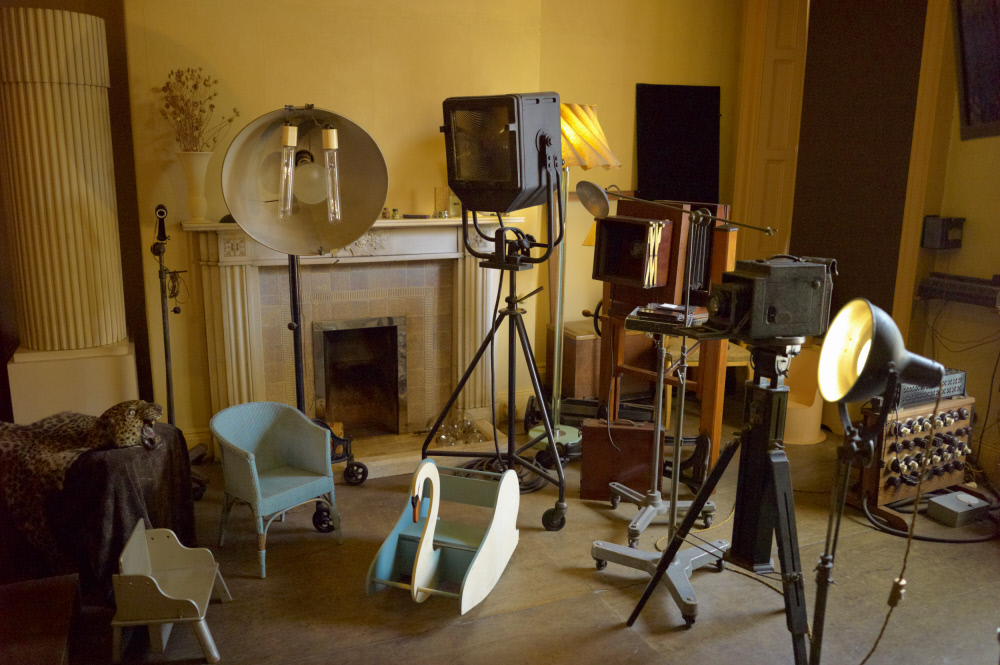 photograph of interior of house set up as photography studio with props, lights and large format camera