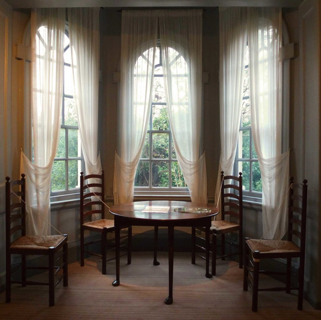photograph of the interior of a period home, showing circular table and four chairs in a bay window