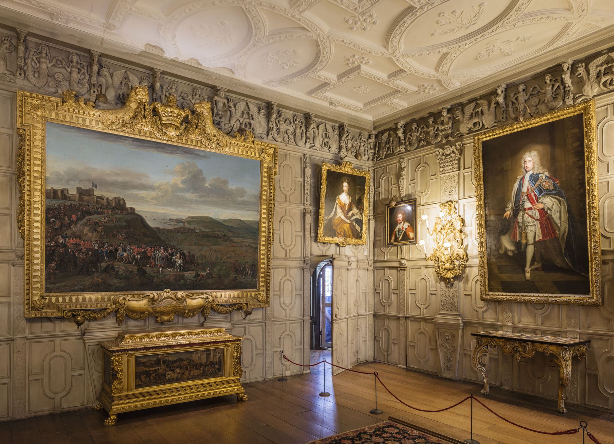 a photo of a panelled room with guilt framed paintings