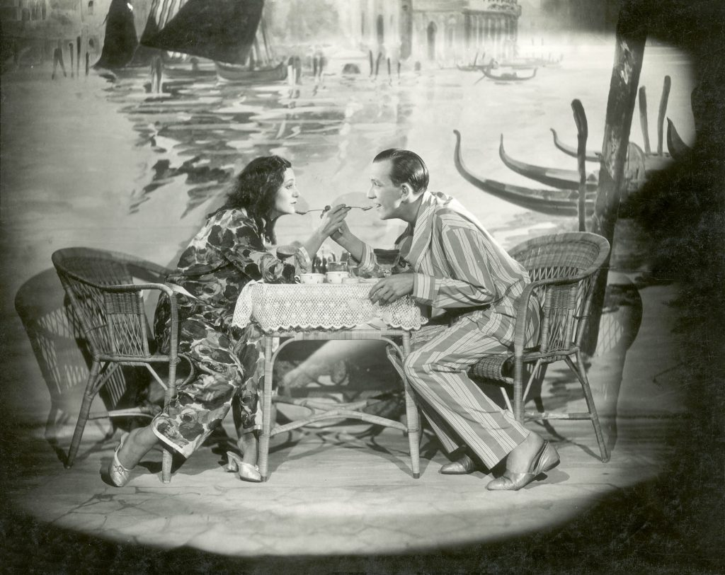 a film still of two people in their lyjamas on a film set