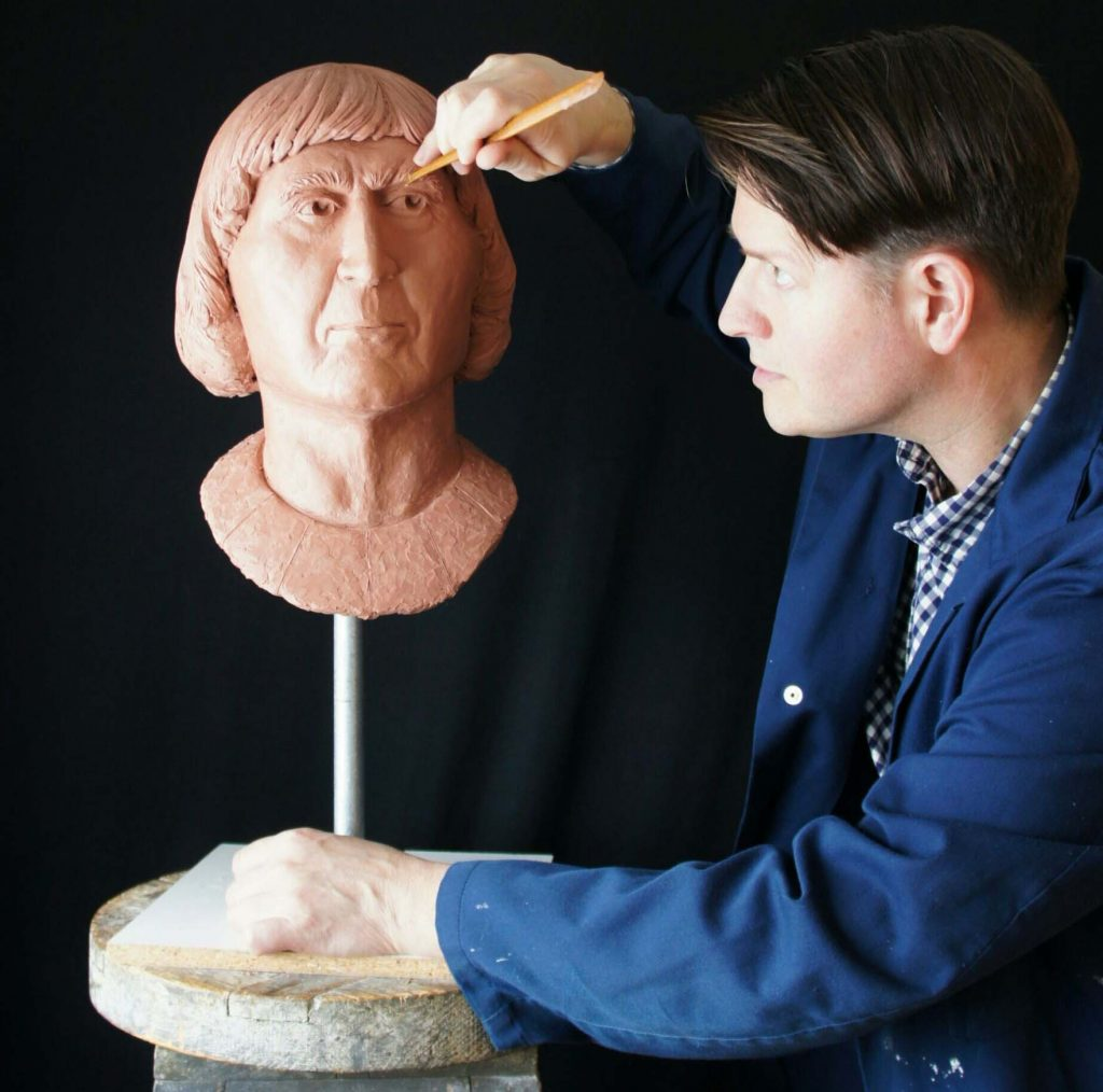 a photo of a man in a potters linen coat using a sculpting tool on a bust of a man with a medieval haircut