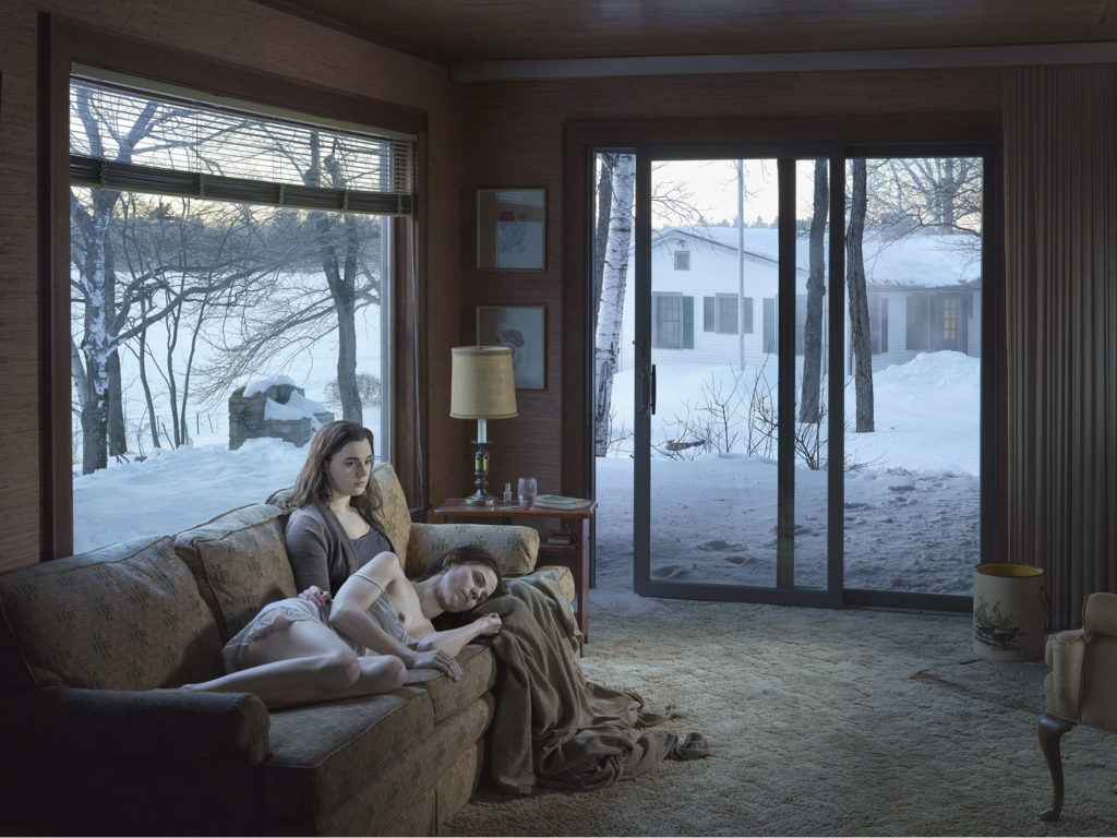 photograph of two women on sofa in lounge with open patio door leading to snowy yard