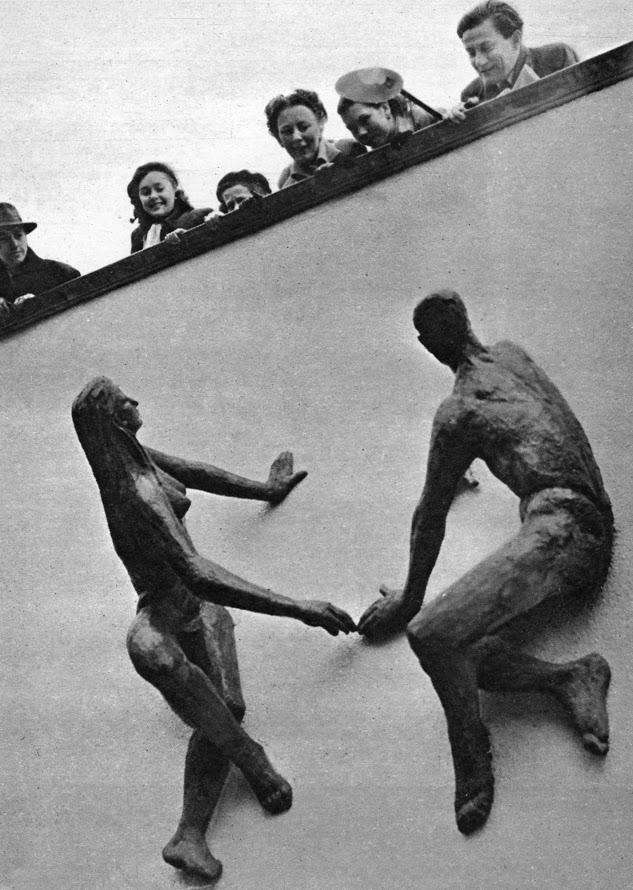 a photo of a group of people peering over a wall at a sculpture of a naked couple