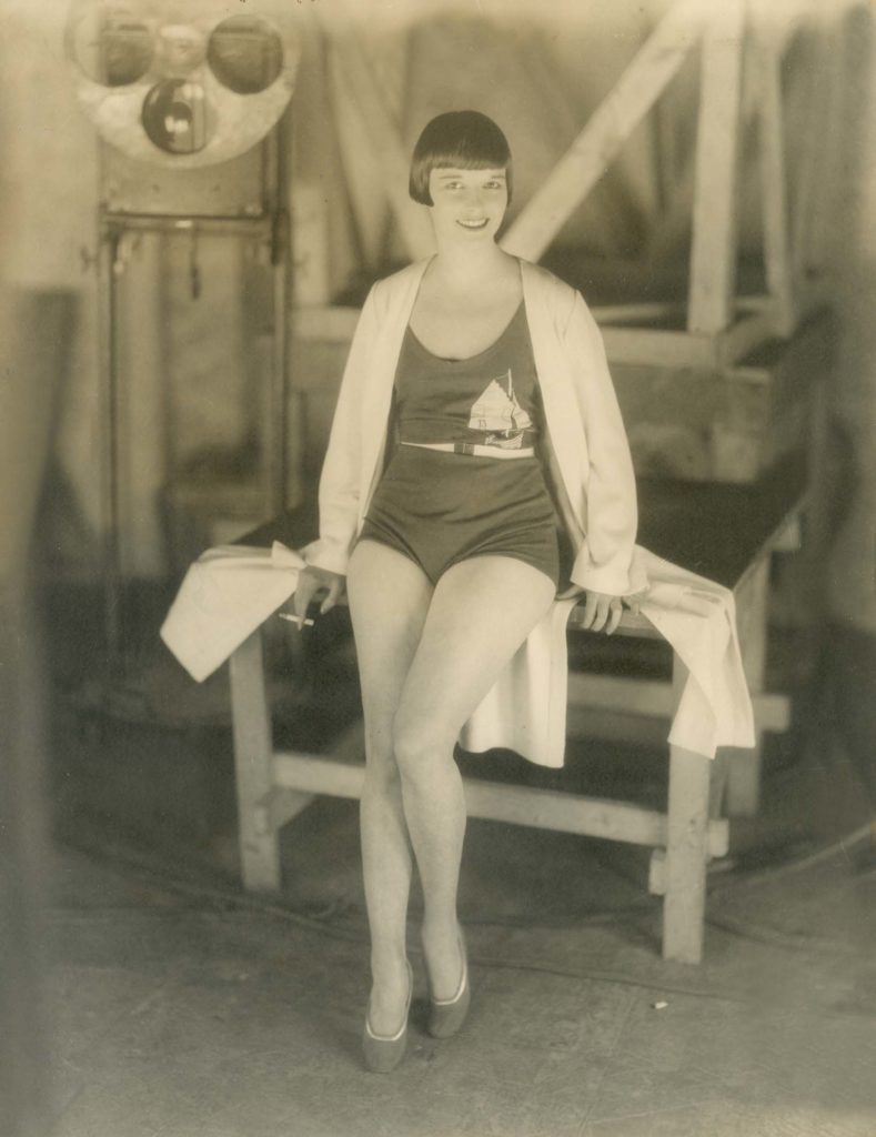 a photo of a woman with bobbed hair wearing a swimsuit and smoking a fag