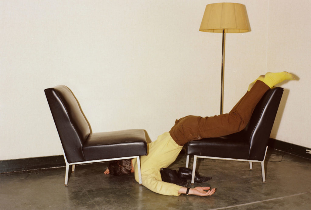photograph of man in yellow and brown lying across two chairs