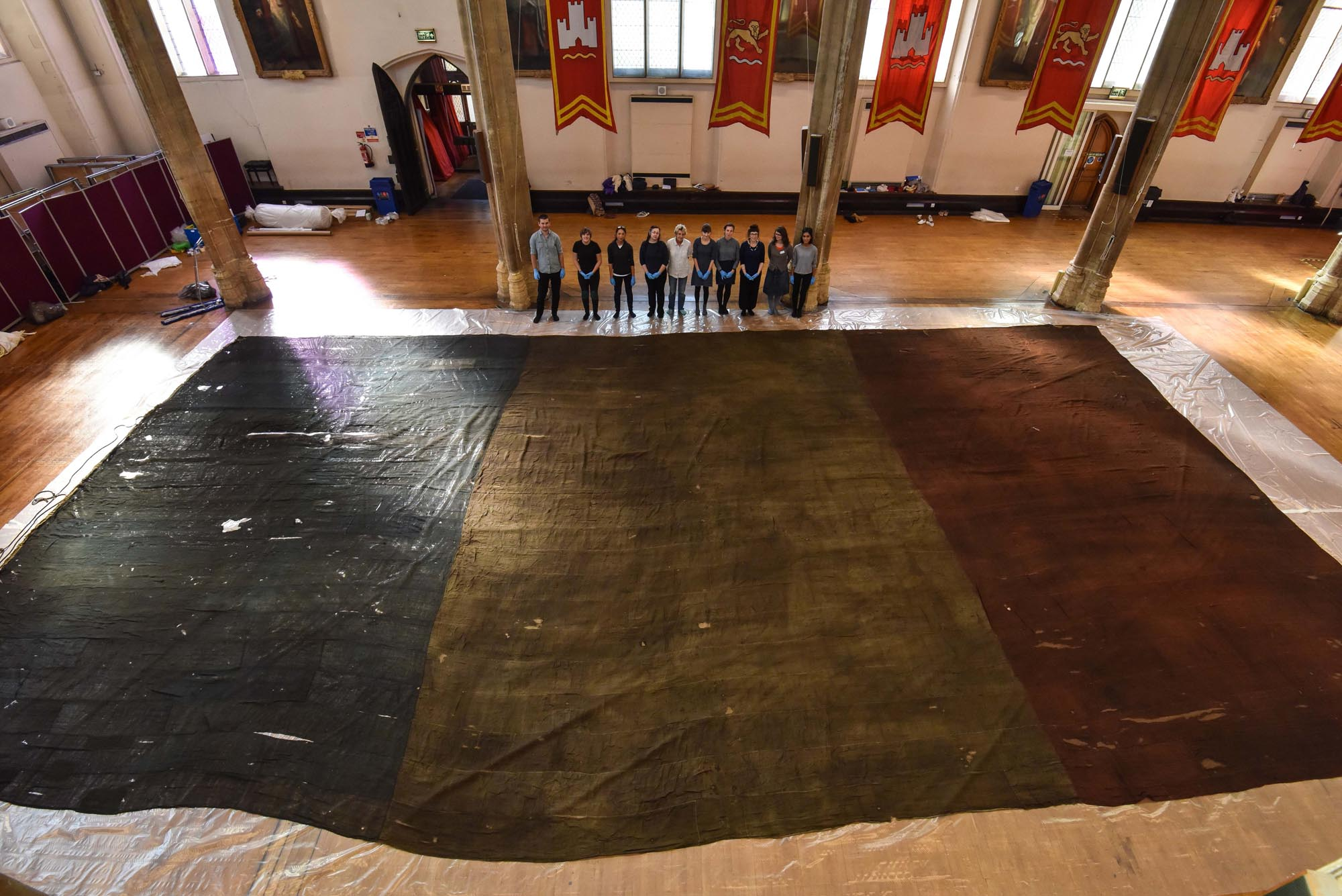 a photo of a vast French tricolor flag laid out in a hallway with people stanidng next to it