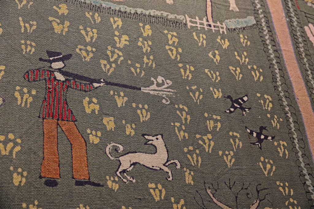 a detail of a wall hanging with a man firing a gun next to a dog
