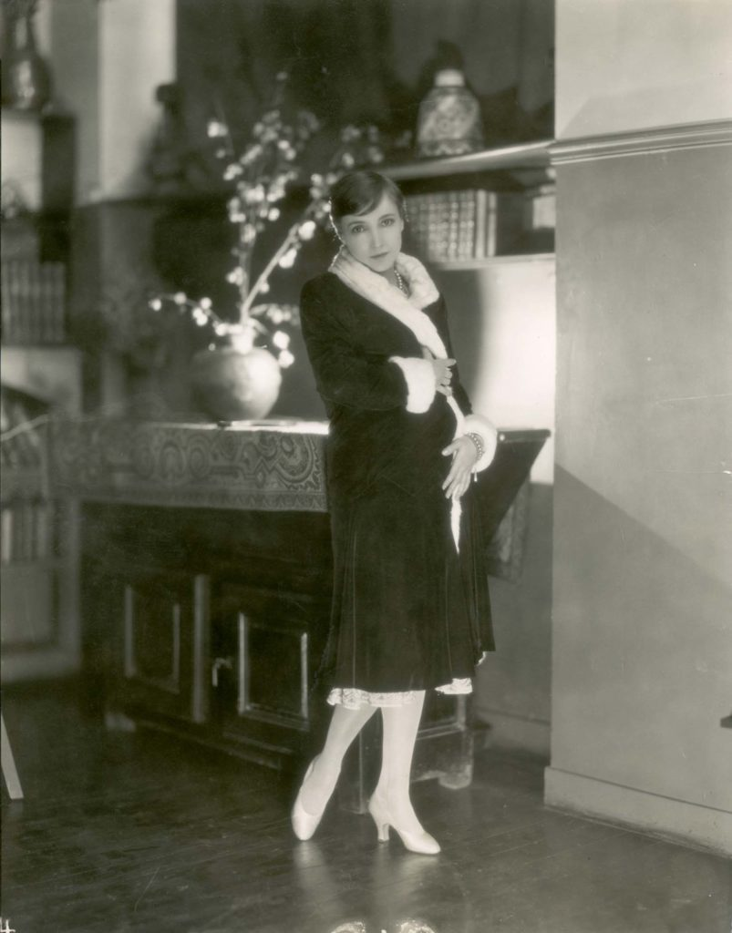 a photo of a woman demurely wearing a fur coat