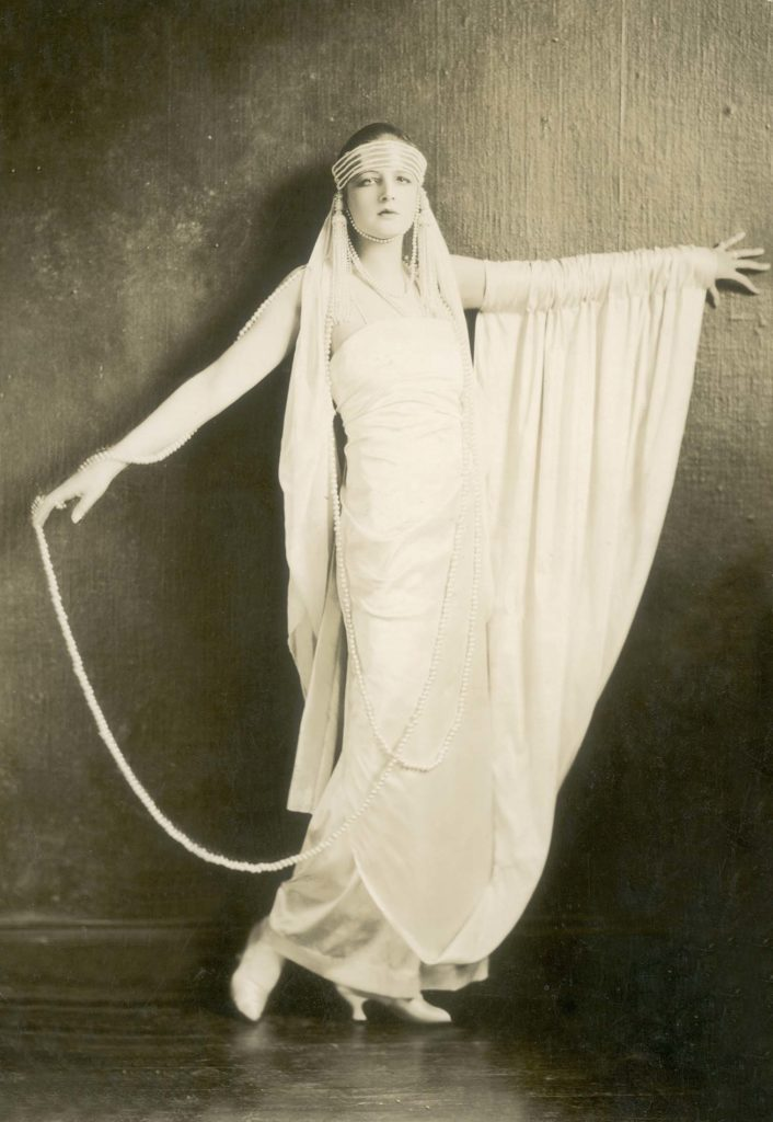 a photo of a glamorous woman in a long dress and headdress