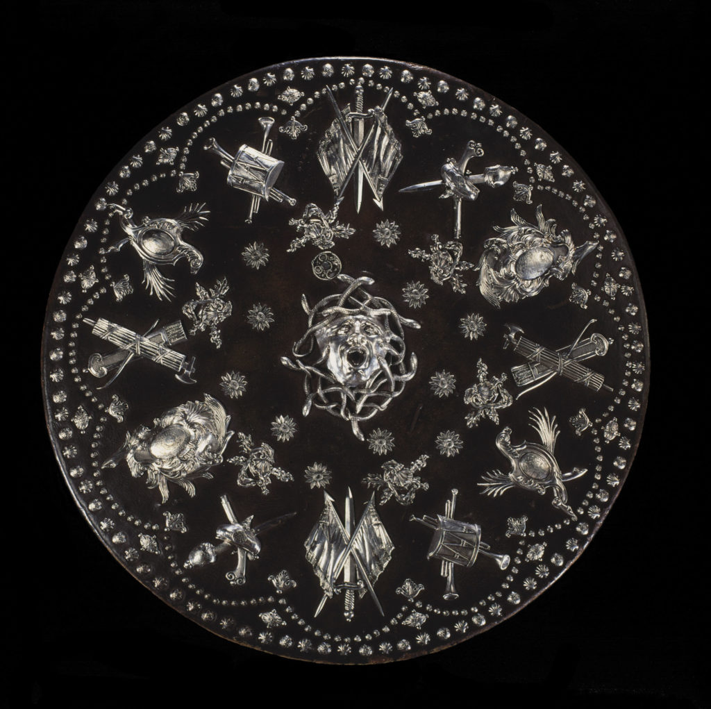 a photo of a round shield embossed with silver figures and symbols