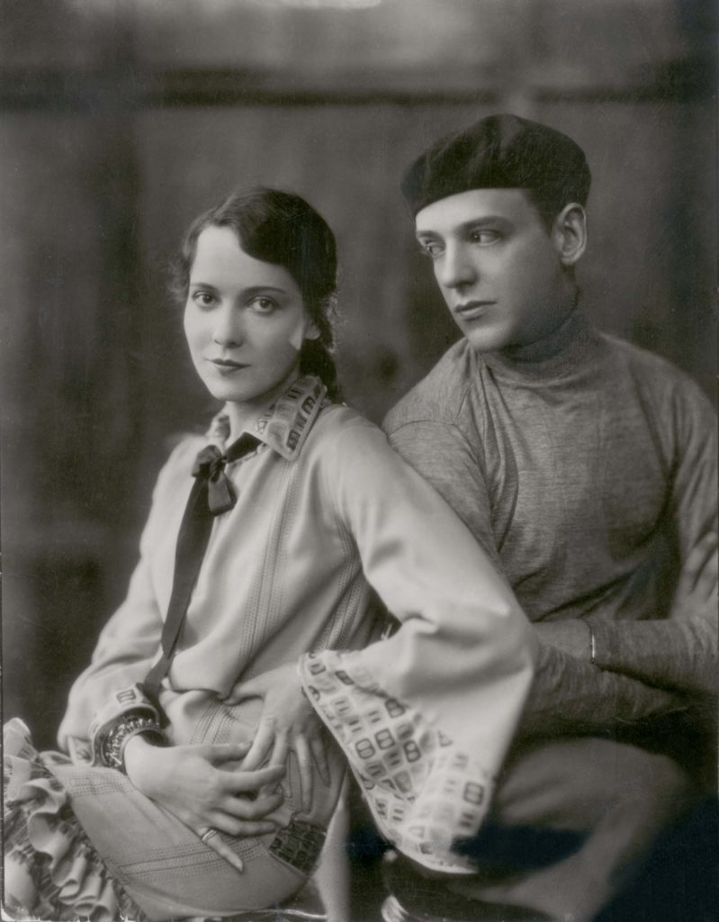 a photo of a man wearing a beret and a woman wearing a silken gown