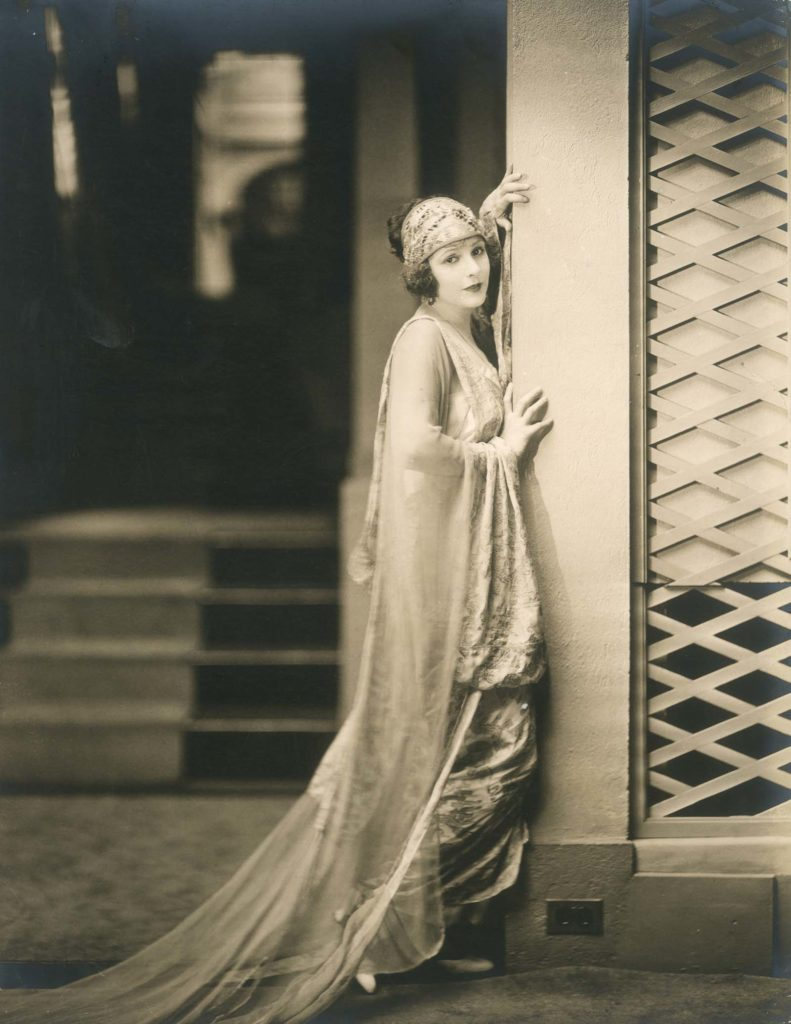 a photo of a woman in a flowing gown leaning against a pillar