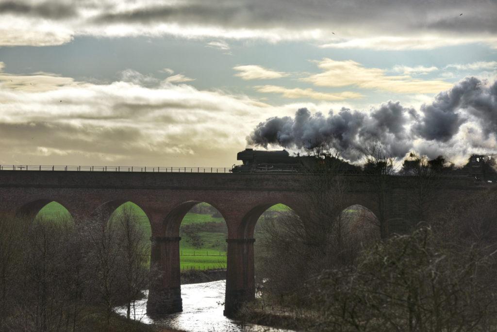 photo of a steam locomotive steaming across a bridge