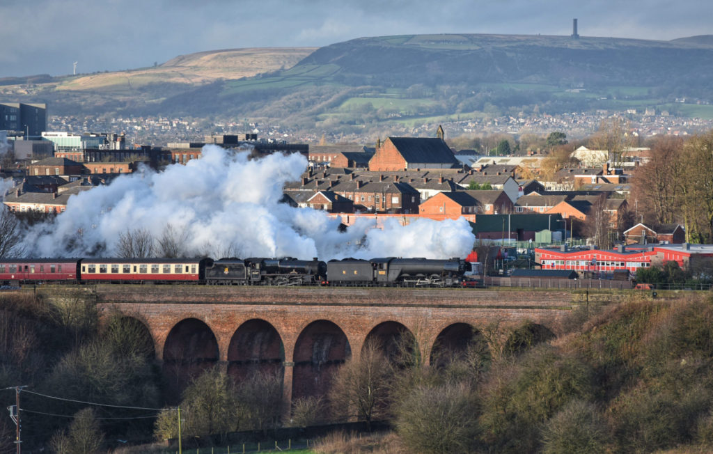 photo of a steam locomotive traveling over bridge over a river