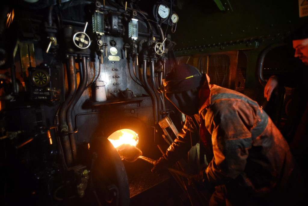 a photo of a man shovelling coal into the boiler on the footplate of a locomotive