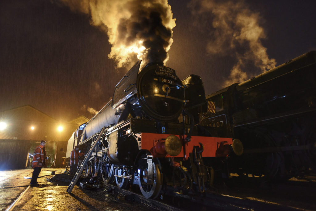 a photo of a steam engine with steam coming from its funnel