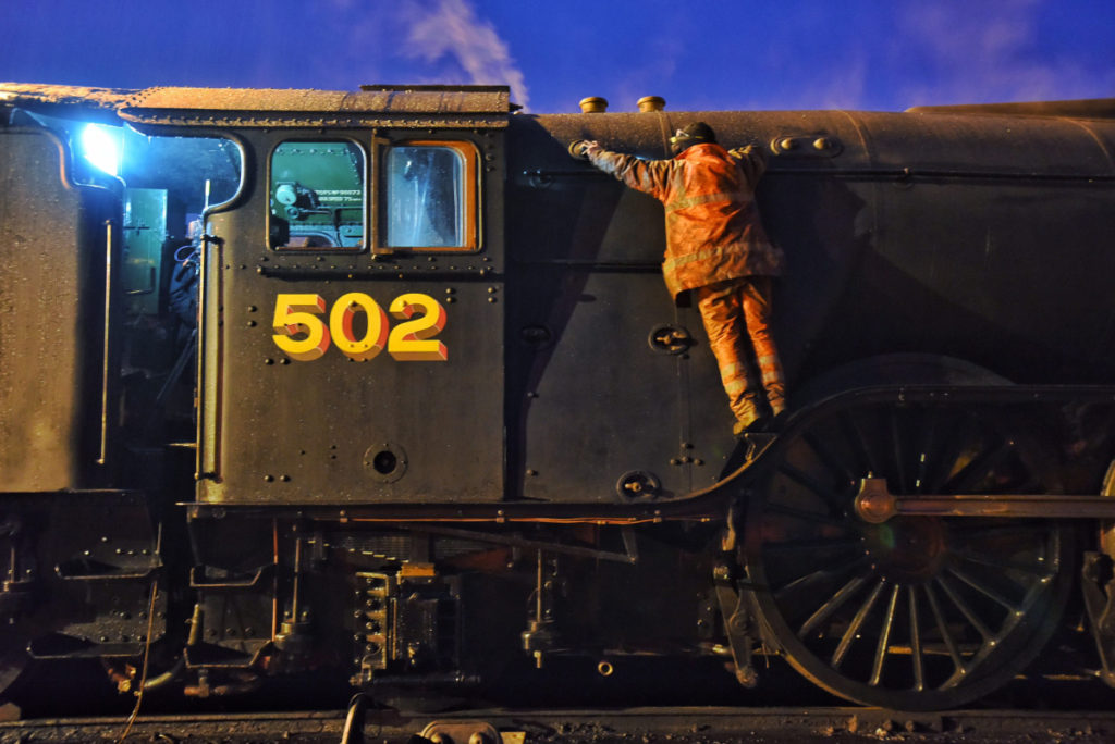 photo of an engineer clinging to the side of a vast locomotive by standing on the main wheel arch
