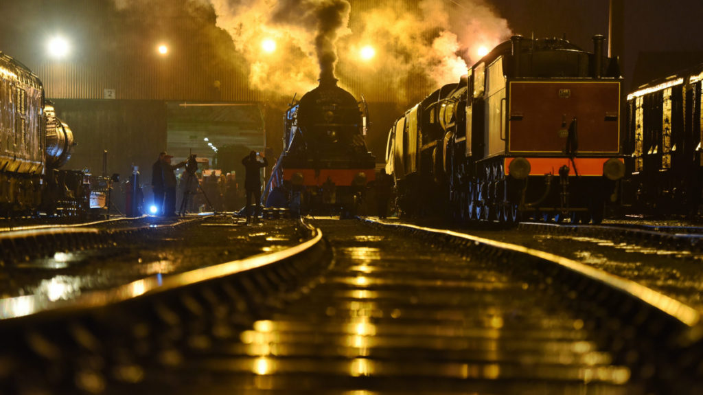 a photo of a steam locomotive pulling out of an engine shed