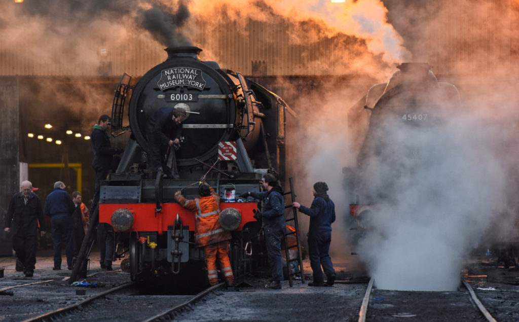 a photo of a locomotive swathed by steam