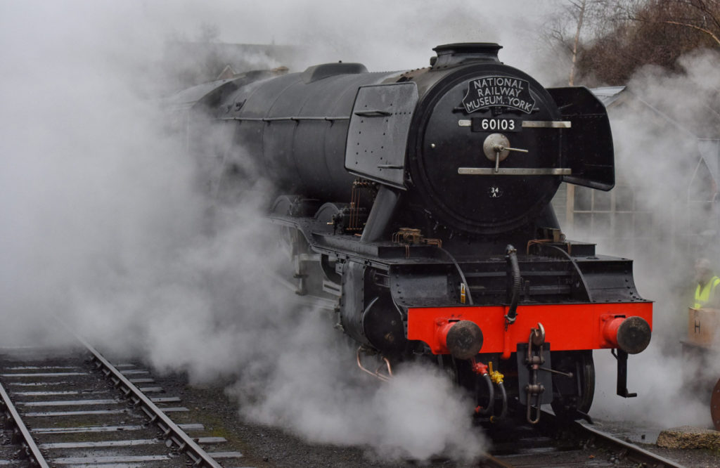photo of a steam locomotive steaming across the tracks