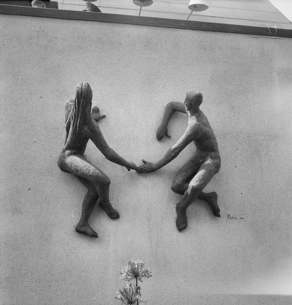 a photo of a csculpture of a naked man and woman fixed to a wall