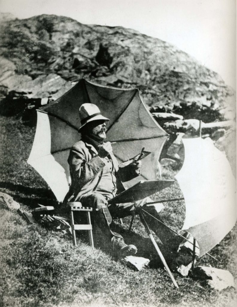 a black and white photo of a man with umbrellas and easel seated on a hillside