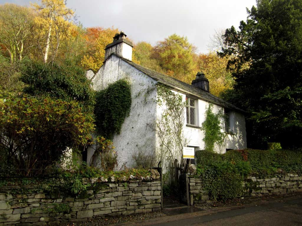 Photograph of exterior of small white rural cottage