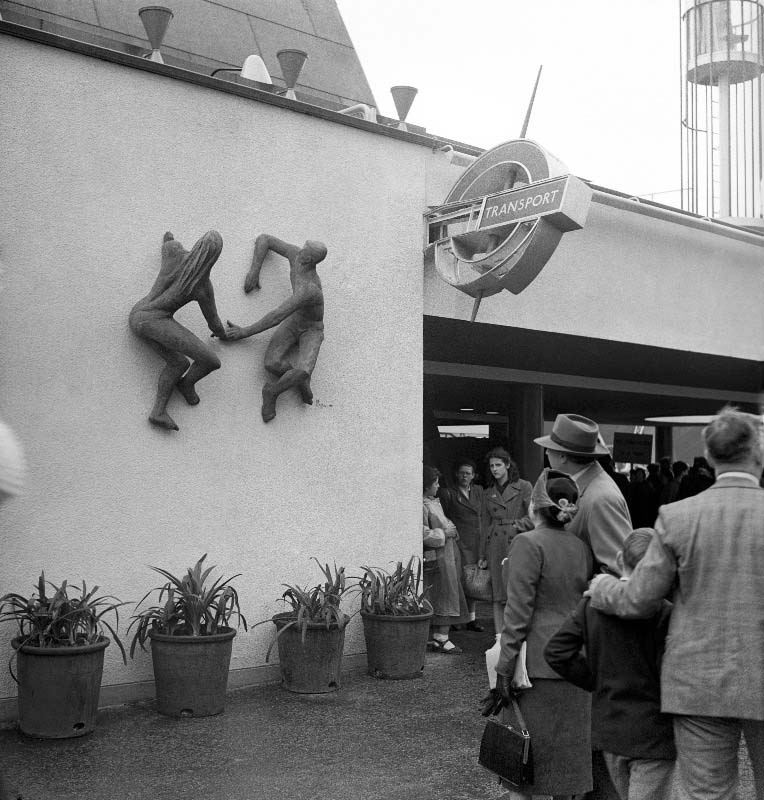 a balck and white photo of people passing through a station exut and looking at a sculpture of a maked couple mounted on the wall