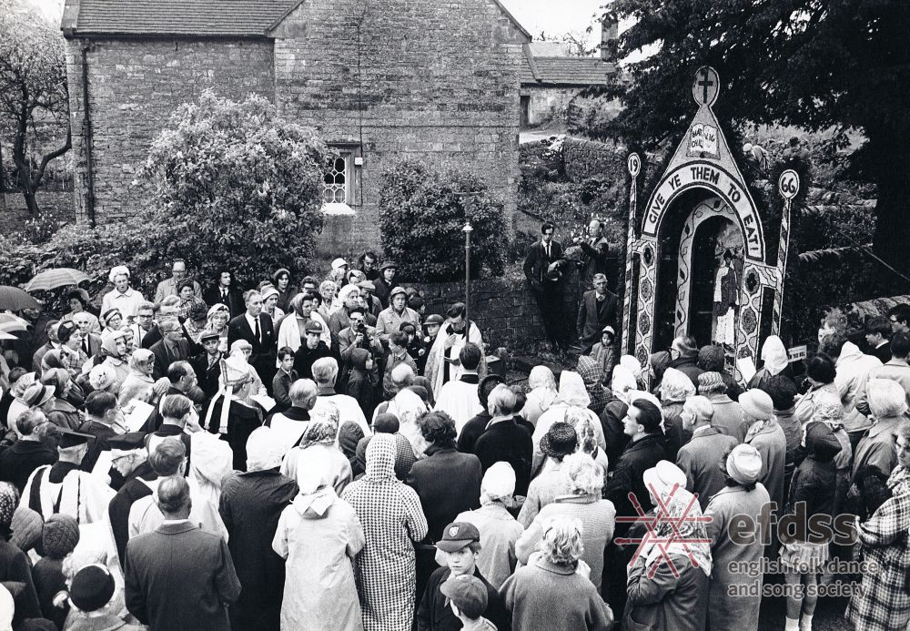 a photo of a group of people stood around a priest in robes around a well dressed like a shrine with flowers