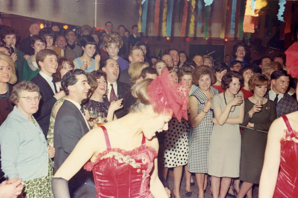 a colour photo of people dancing watched by a group of men and women dancing
