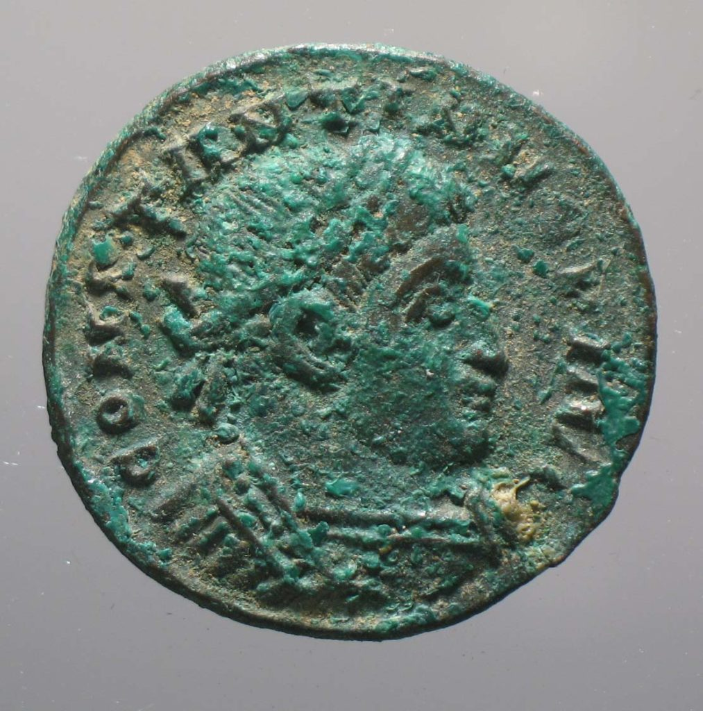 a photo of a roman coin with an Emperor's head on it.