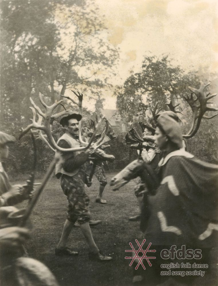 a photo of men in berets and plus fours carrying stag horns and dancing