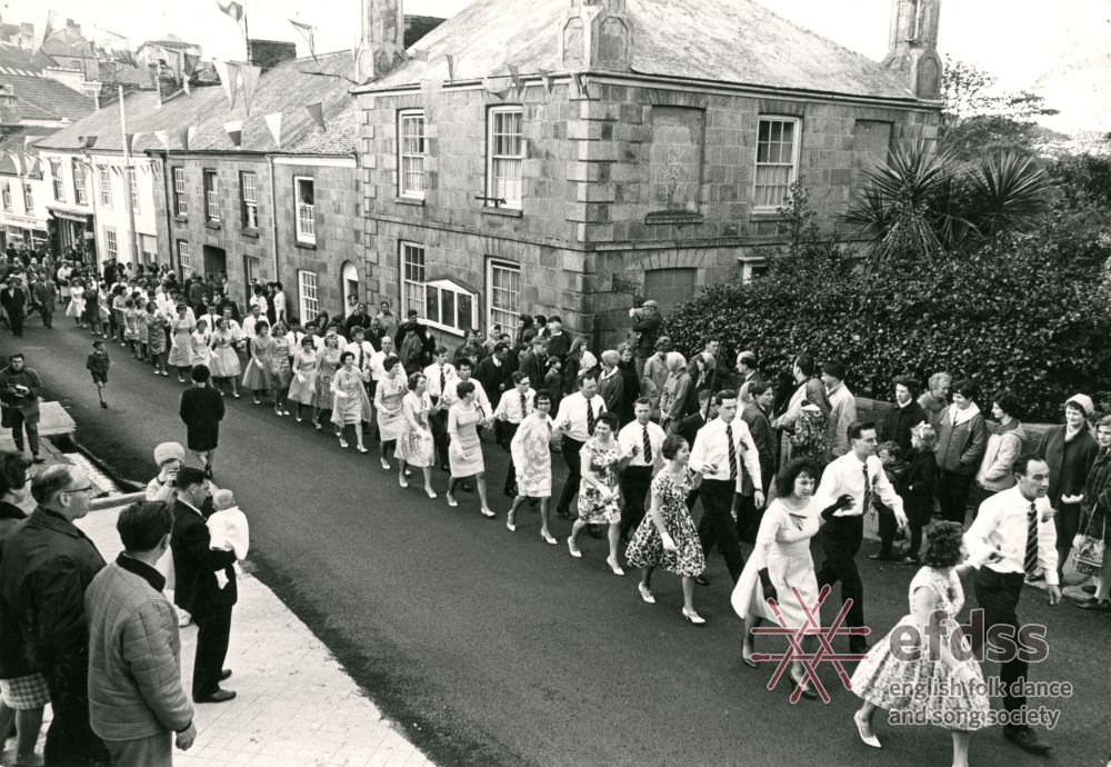 a photo of a parade of young men and women walking through a street past a pub