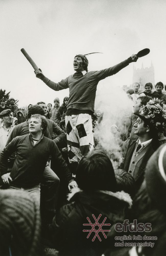 a photo of man standing above a steaming crowd whilst gesticulating with a stick