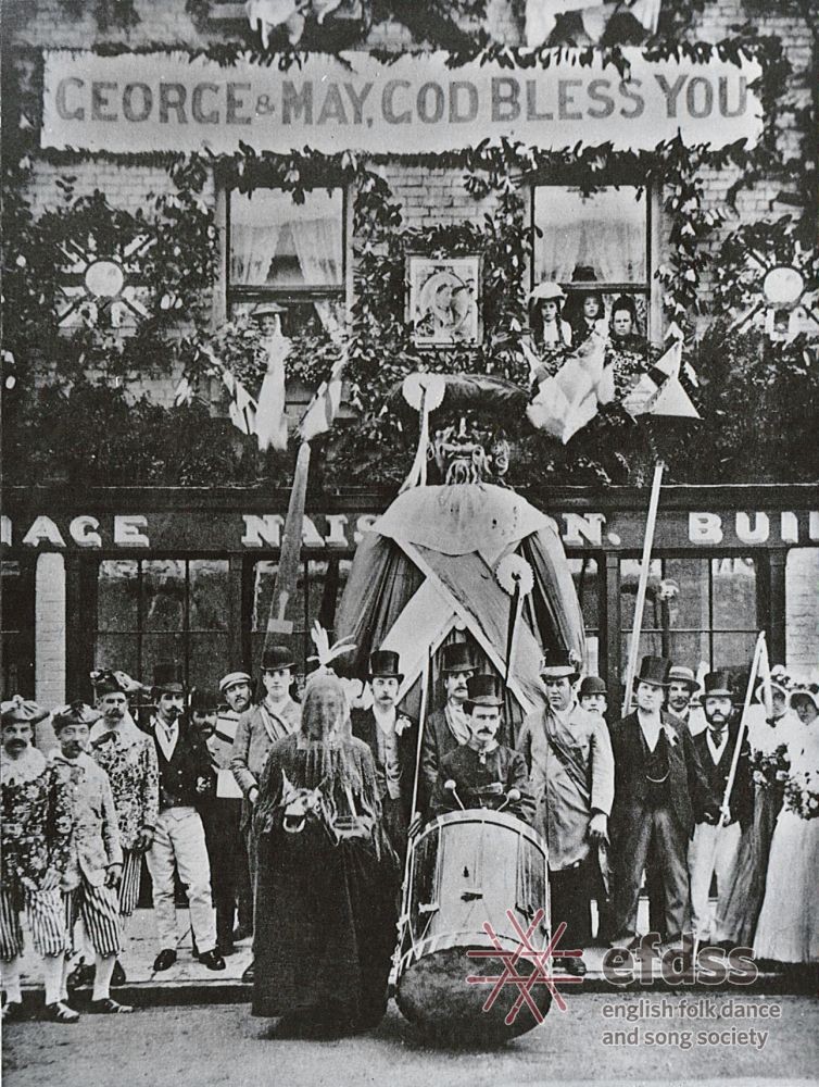 A photo of a group of people standing outside a village shop next to a model of a giant man